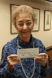 Marcie Leitzke, the last active founding member of the Shawano Area Writers, holds up a $77,090.32 check from the estate of George Putz that the group received in October. Putz's will designated that the money should go toward reviving the group's annual writing contest. (Photo by Lee Pulaski)