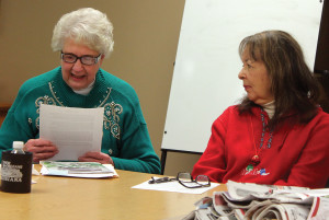 Carol Schlehlein, left, reads a short story she wrote as Trilby Beauprey McIntosh listens during a meeting of the Shawano Area Writers. Schlehlein has self-published two books in the last two years. (Photo by Lee Pulaski)